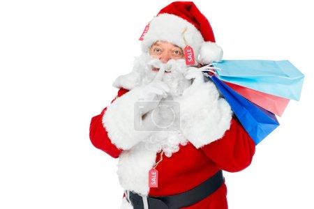 Photo pour Santa claus costume rouge avec des étiquettes de vente maintenant des sacs à provisions et montrant le geste de silence isolé sur blanc - image libre de droit
