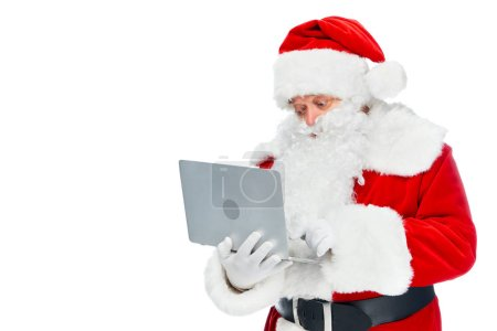 bearded santa claus in red costume using laptop isolated on white