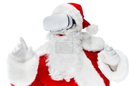 Photo for Bearded santa claus gesturing and using virtual reality headset isolated on white - Royalty Free Image