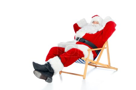 happy santa claus relaxing on beach chair on white