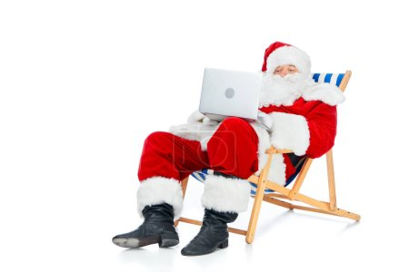 Photo for Santa claus using laptop while resting on beach chair isolated on white - Royalty Free Image