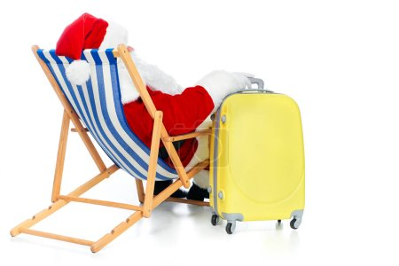 back view of santa claus resting in beach chair with travel bag on white