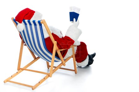 rear view of santa claus holding two passports and air tickets for christmas trip while sitting in beach chair isolated on white