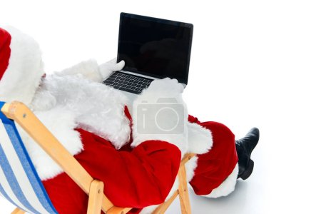 santa claus using laptop with blank screen while resting on beach chair isolated on white