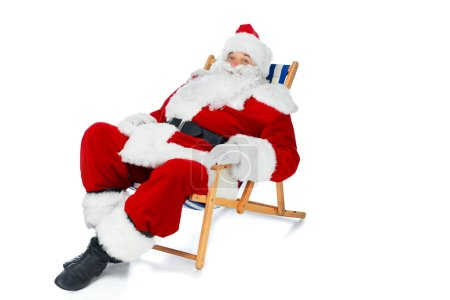 Photo for Happy santa claus resting on beach chair on white - Royalty Free Image