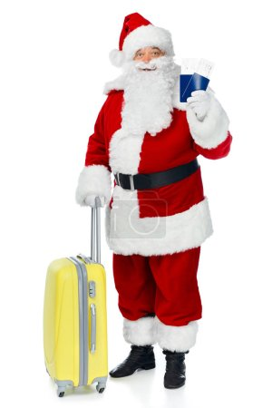 santa claus with travel bag holding two passports and air tickets for christmas trip isolated on white