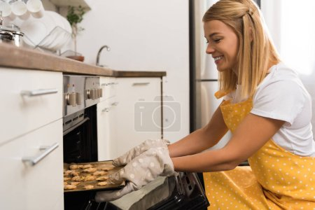Photo for Side view of smiling young woman in apron putting baking tray with cookies in oven - Royalty Free Image