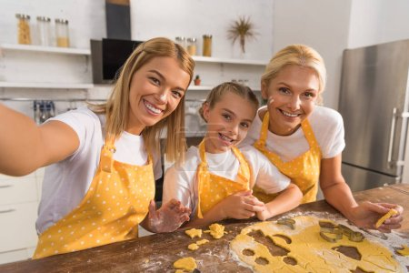 happy child with mother and grandmother smiling at camera while preparing cookies together in kitchen