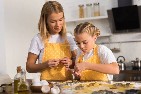 Photo for Beautiful mother and daughter in aprons preparing cookies together in kitchen - Royalty Free Image