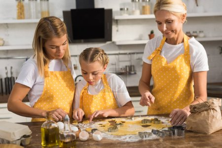beautiful three generation family in aprons preparing cookies together in kitchen