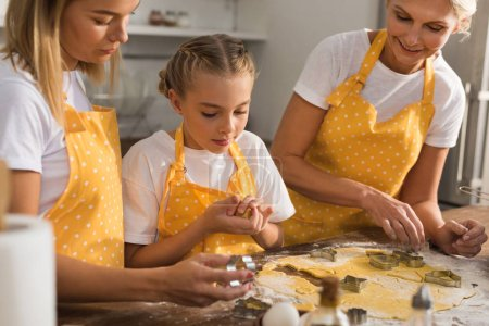 cute preteen kid with mother and grandmother preparing cookies together