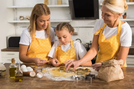 happy three generation family in aprons preparing cookies together
