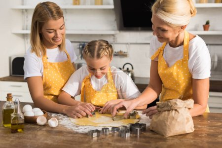 happy child with mother and grandmother preparing cookies together in kitchen