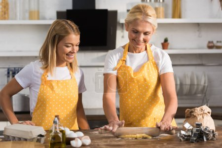 happy mature woman with adult daughter preparing dough together in kitchen