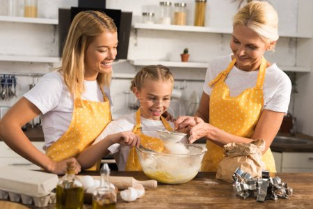 happy child with mother and grandmother preparing dough together