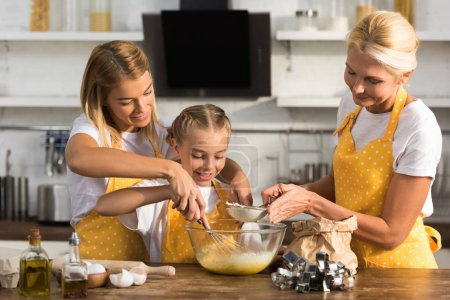 adorable happy child with mother and grandmother preparing dough together in kitchen