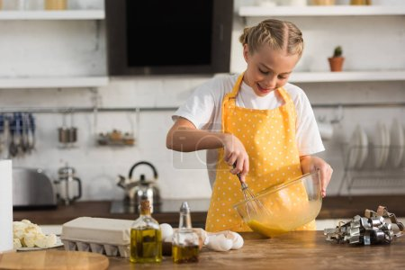 adorable smiling chuild in apron whisking eggs while cooking in kitchen