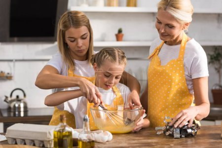 cute child with mother and grandmother whisking eggs while cooking together