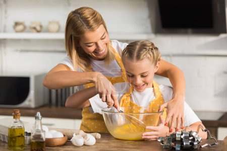 happy mother and daughter whisking eggs while cooking together