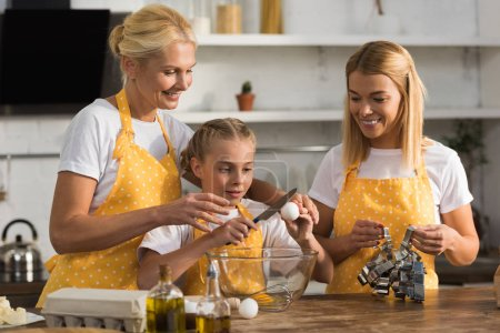 happy three generation family preparing dough together in kitchen