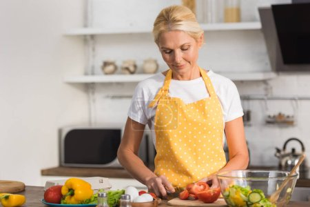 beautiful mature woman in apron cooking vegetable salad in kitchen