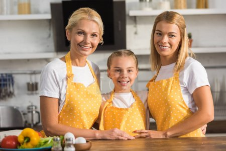 happy three generation family in aprons smiling at camera in kitchen