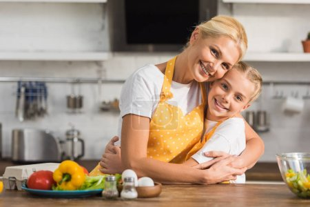 happy grandmother and granddaughter in aprons hugging and smiling at camera while cooking together