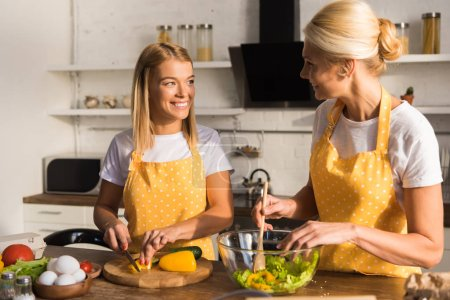 Photo for Happy adult mother and daughter smiling each other while cooking together in kitchen - Royalty Free Image