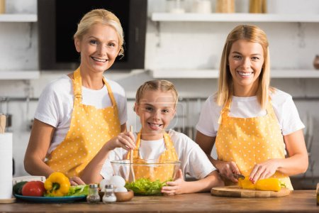 adorable happy child with mother and granmother smiling at camera while cooking together
