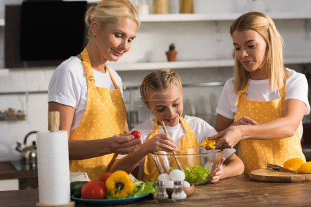 cute happy child with mother and grandmother cooking vegetable salad together in kitchen