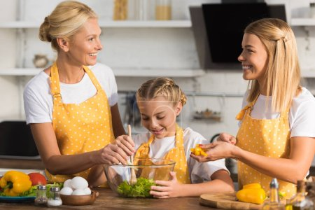 happy three generation family cooking vegetable salad together