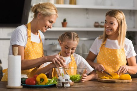 Photo for Happy child cooking with mother and grandmother in kitchen - Royalty Free Image