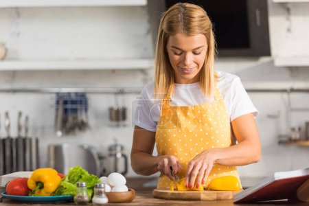Photo for Smiling young woman in apron cutting vegetables in kitchen - Royalty Free Image