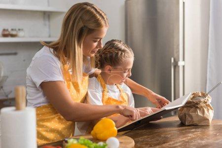 mère et fille en tabliers lire livre de recettes et cuisine ensemble
