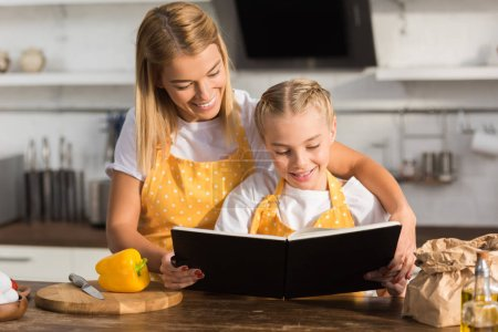 Photo for Happy mother and daughter reading cookbook while cooking together - Royalty Free Image