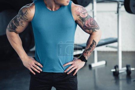Ausgeschnittener Blick auf jungen tätowierten Sportler im Fitnessstudio