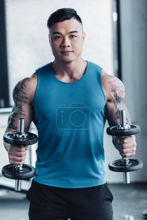 concentrated young asian sportsman exercising with dumbbells in gym concentrarted