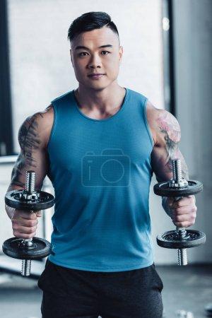 concentré de jeune sportif asiatique exercice avec des haltères dans la salle de gym concentrarted
