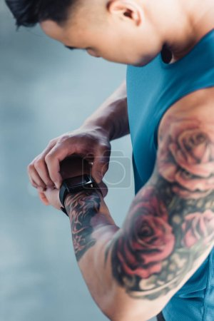 cropped view of young sportsman after long workout looking at watch