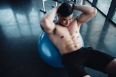 focused young asian sportsman with bare chest doing abs exercise on fitness ball at gym