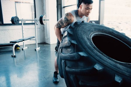 focused young sportsman flipping heavy tire at gym