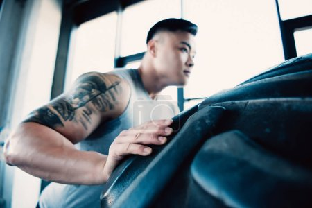concentrated young sportsman flipping heavy tire at gym