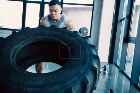 Photo for Concentrated young sportsman flipping heavy tire at gym - Royalty Free Image