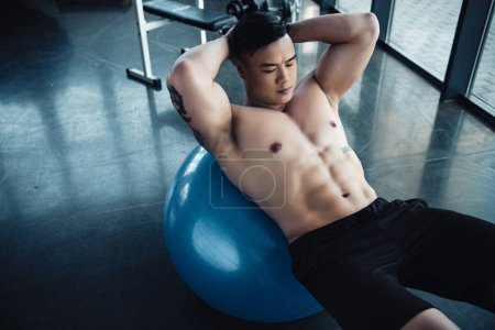 young sportsman with bare chest doing abs exercise on fitness ball at gym