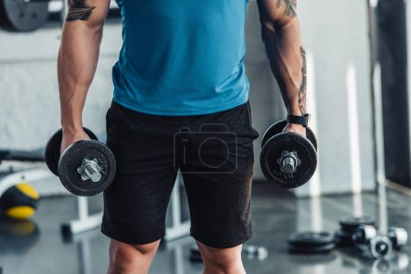 midsection of young sportsman exercising with dumbbells in gym