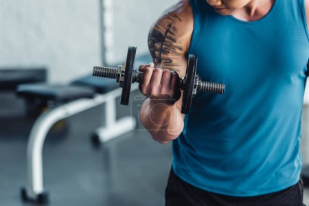 close up view of young sportsman exercising with dumbbell in gym