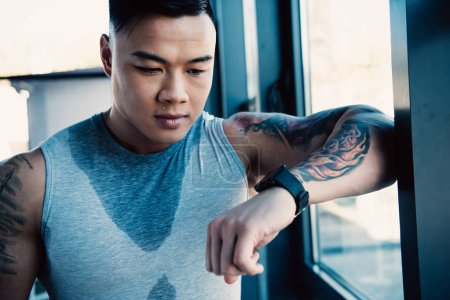 young sweaty tired asian sportsman after long workout looking at watch