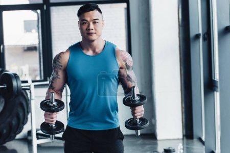 Photo pour Concentré de jeune sportif asiatique exercice avec des haltères dans la salle de gym - image libre de droit
