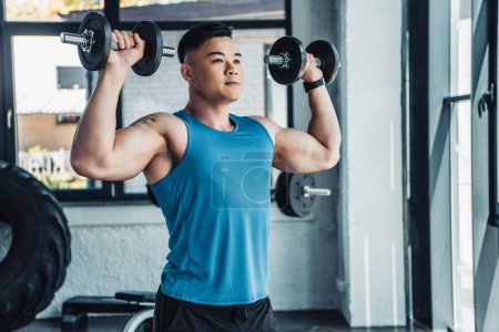 Photo for Concentrated young asian sportsman exercising with dumbbells in gym - Royalty Free Image