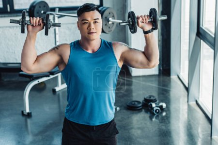 concentrated young sportsman exercising with dumbbells in gym and looking at camera